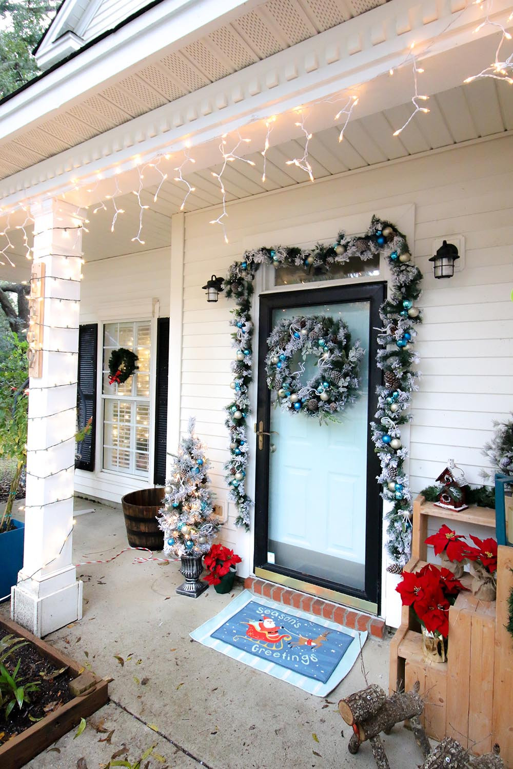 A holiday porch refresh with flocked garland, a wreath, and icicle lights.
