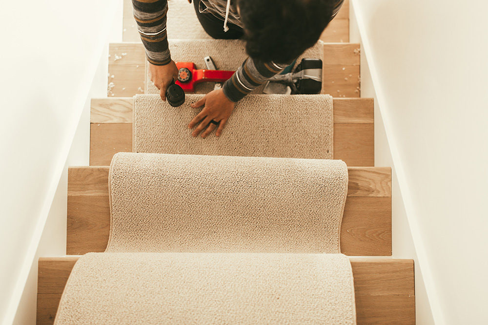 A person adding carpet to stair case