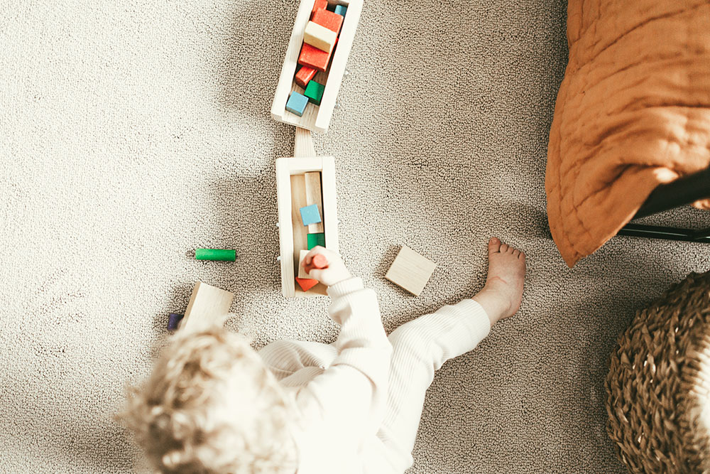 a person playing toys on carpet