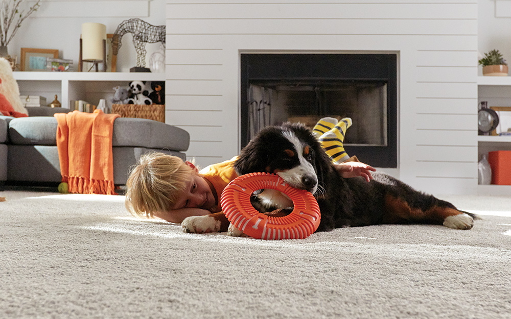 A boy and a puppy lying on a grey carpet in a living room.