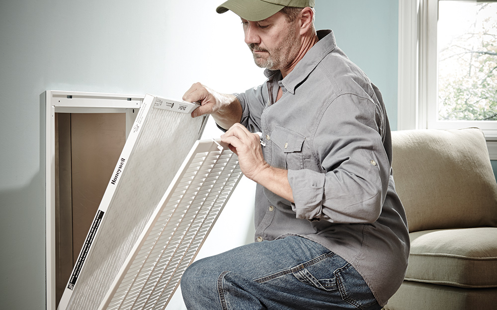 a man replacing an air filter inside the home