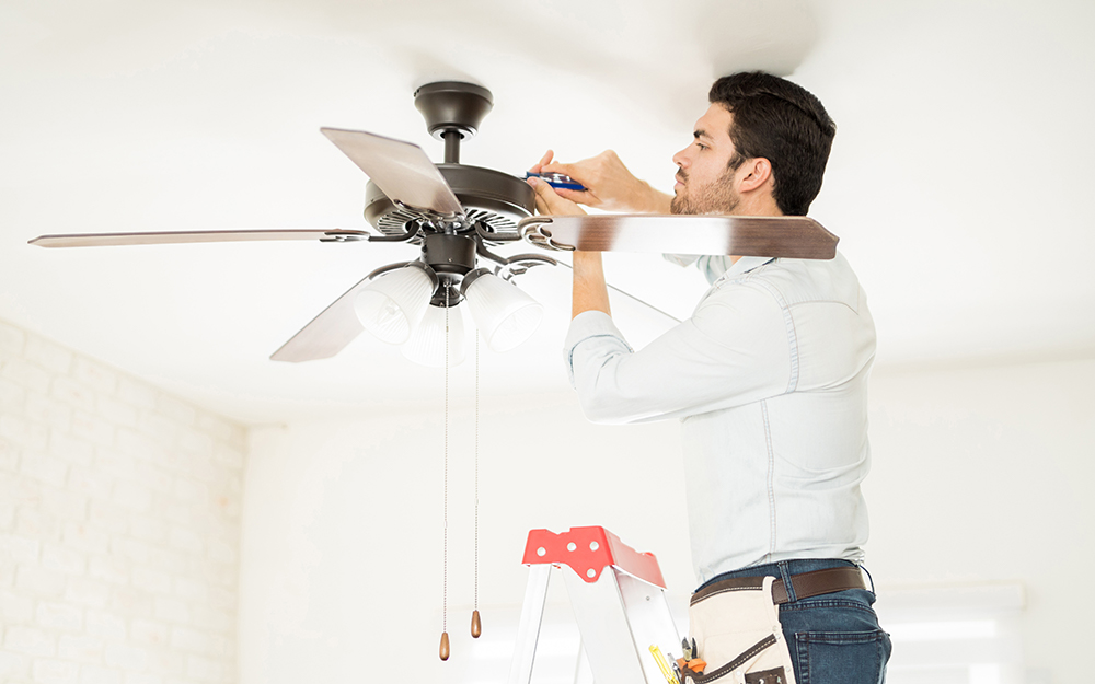 A man on a ladder adjusting ceiling fan housing with a screwdriver.