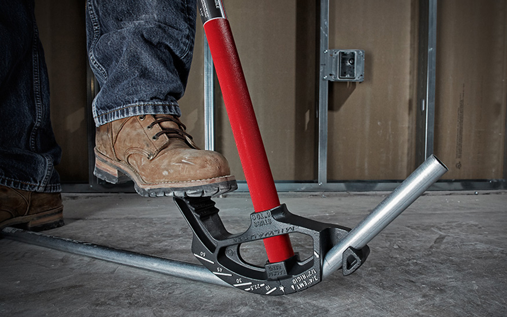 A person uses his boot to steady a conduit bender as it bends a pipe.