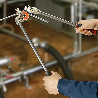A person bends metal tubing in a manual bender.