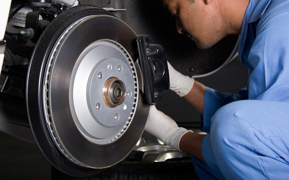 Một người đàn ông đang tháo một phần của phanh xe ô tô