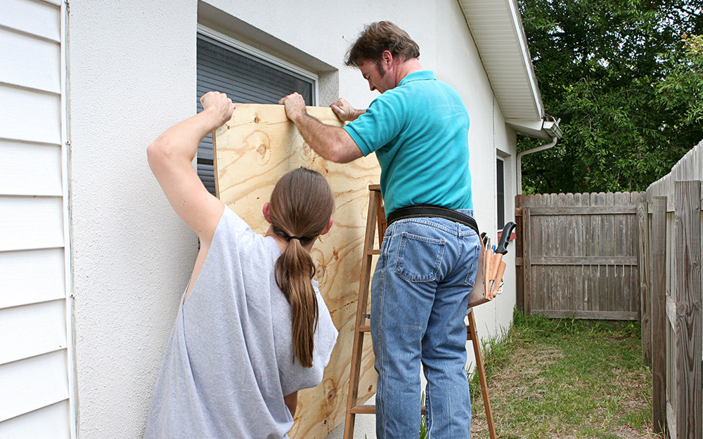 People lift a piece of plywood to install over the windows of a home.