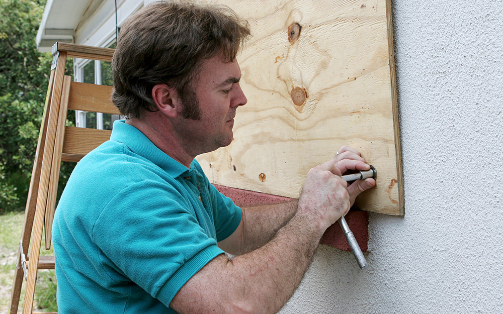 A person installs a piece of plywood over the window of a home.