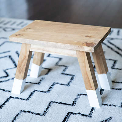 A wooden stool on top of a rug.