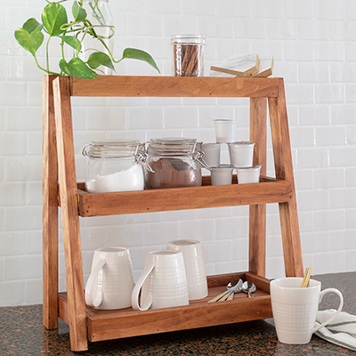 A tiered organizer with cups and mugs.