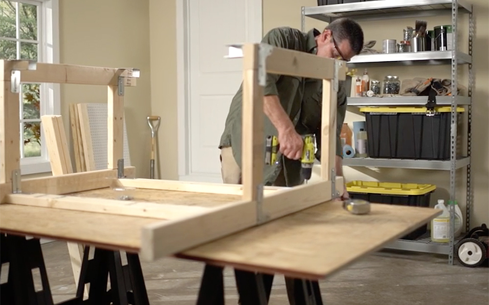 A person drilling the frame of a workbench.