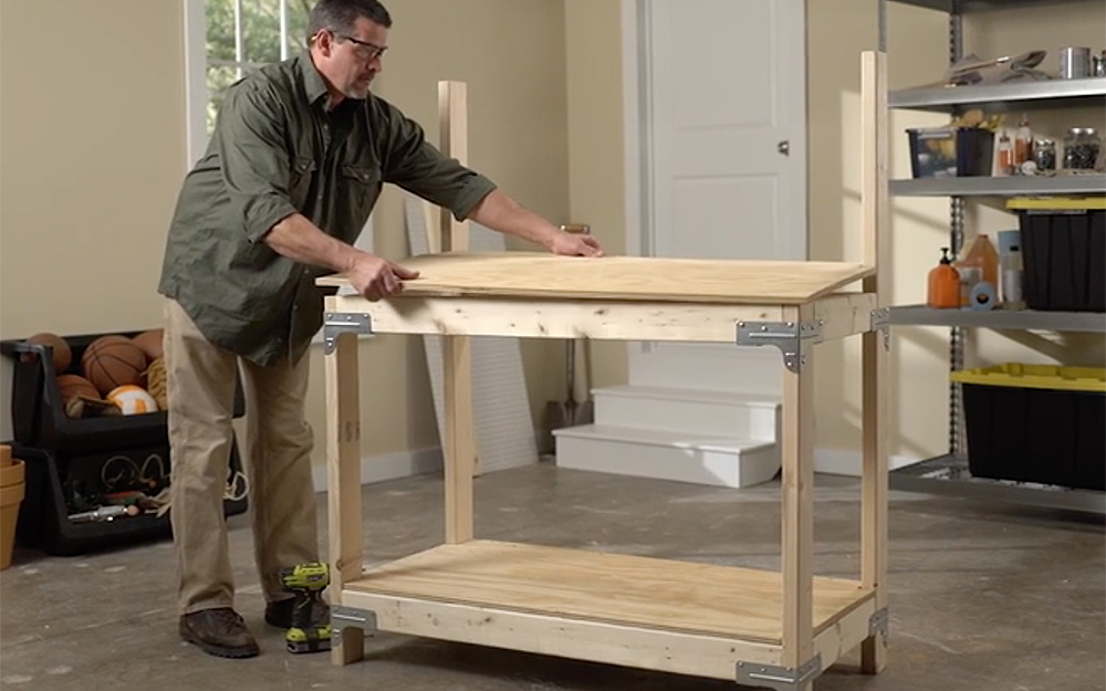 A person installing a shelf on a workbench.