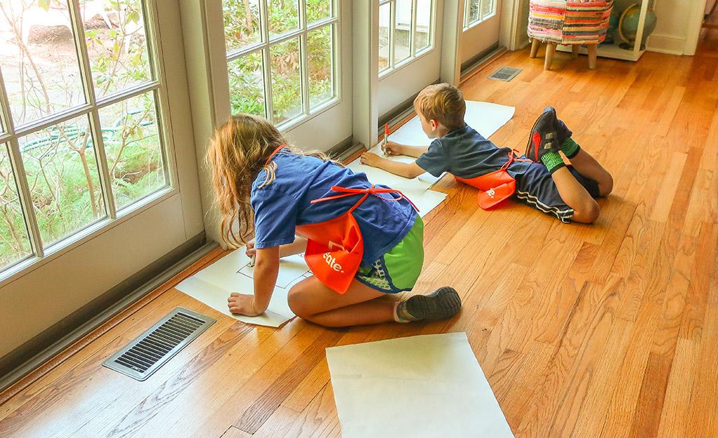 Hai đứa trẻ đang vẽ trên giấy trên sàn nhà.