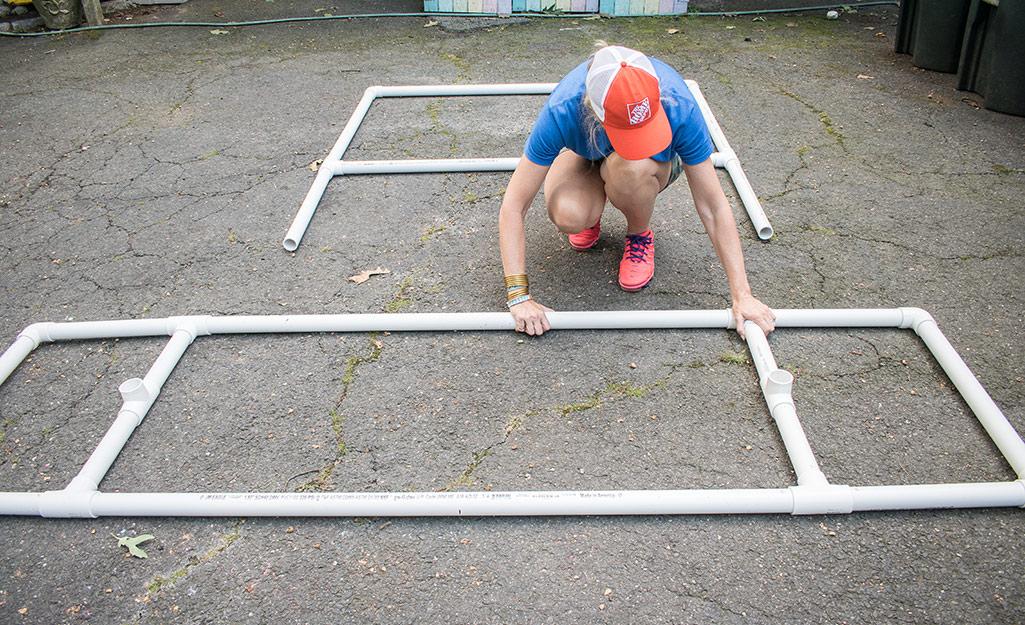 Một người đang lắp ráp ống nhựa PVC trong hình dạng của một màn hình chiếu phim.