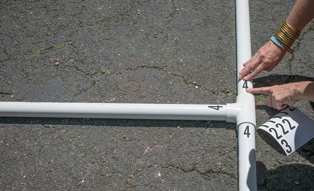 Một người dán nhãn ống PVC với số.