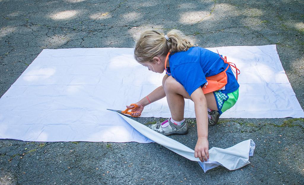 Một cô gái trẻ đang cắt một mảnh rèm.