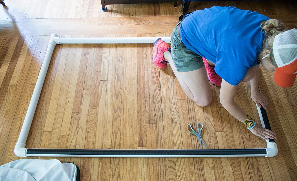 Một người phụ nữ dán băng dính vào các đoạn ống PVC đã sắp xếp.