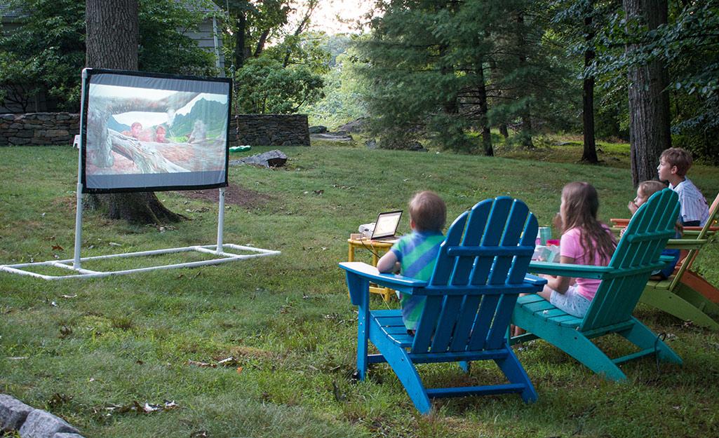Một nhóm trẻ em đang xem phim trên màn hình ở sân sau.