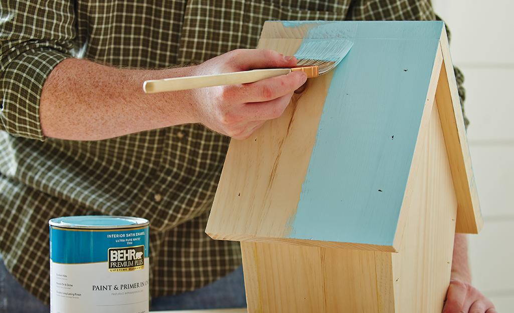 Một người sơn mái nhà chim.