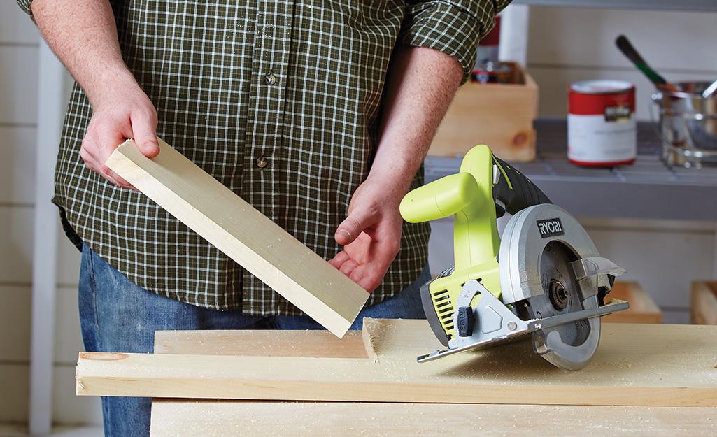 Một người xử lý một mảnh gỗ cho một chuồng chim.
