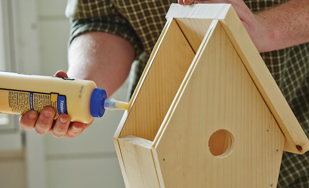 một người bôi keo để gắn mái nhà của một chuồng chim.