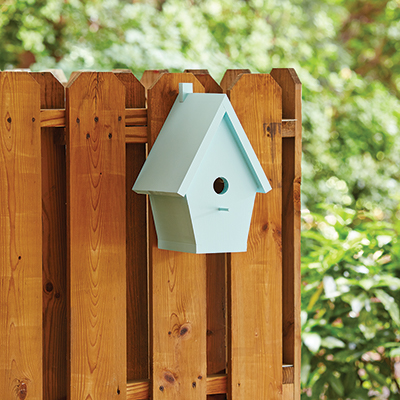 A DIY birdhouse hanging on a fence.