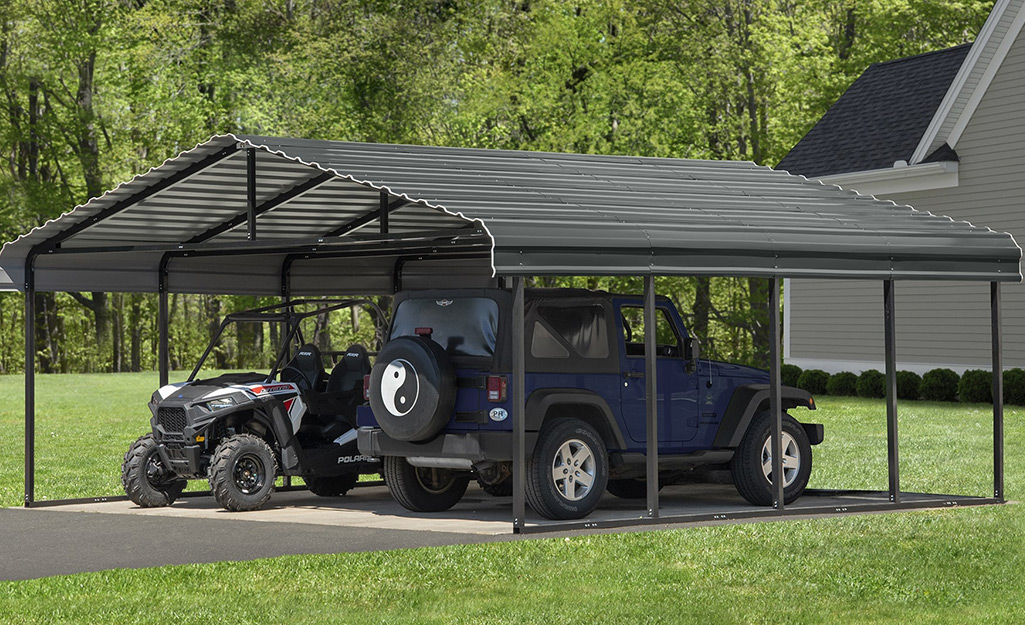 A Jeep and an ATV part side-by-side in a metal carport.