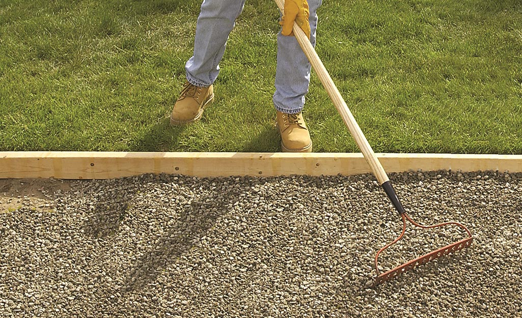 A person uses a metal rake to flatten an area of gravel ground cover.