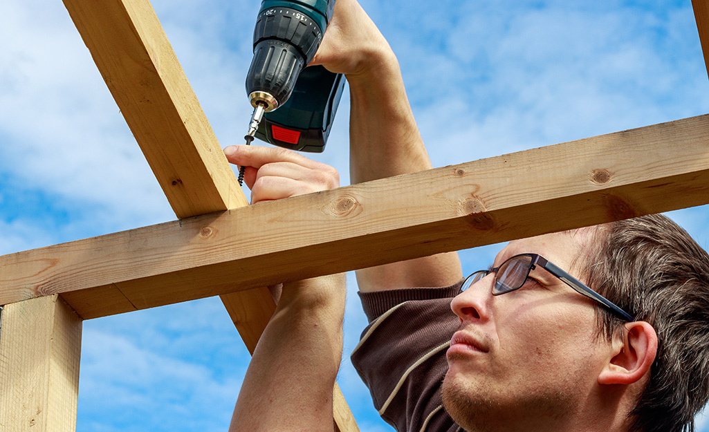 A person uses a power drill to attach a rafter to a beam.