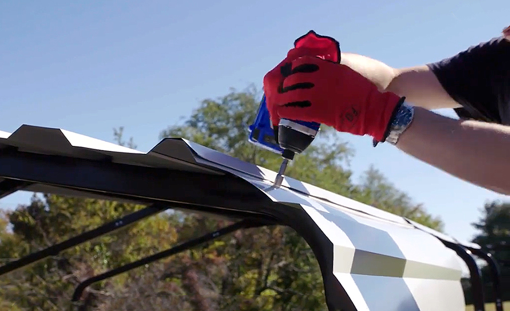 A person use a power drill to attach the roof panels to a metal carport.