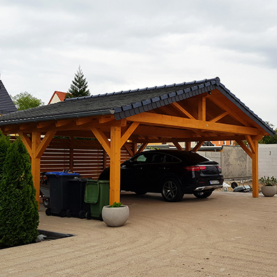 A car parks in the shelter of a wooden carport.