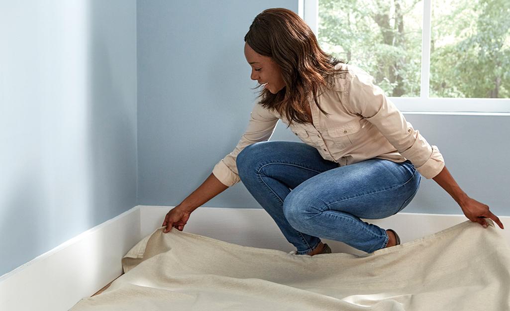 A woman lays down a drop cloth.