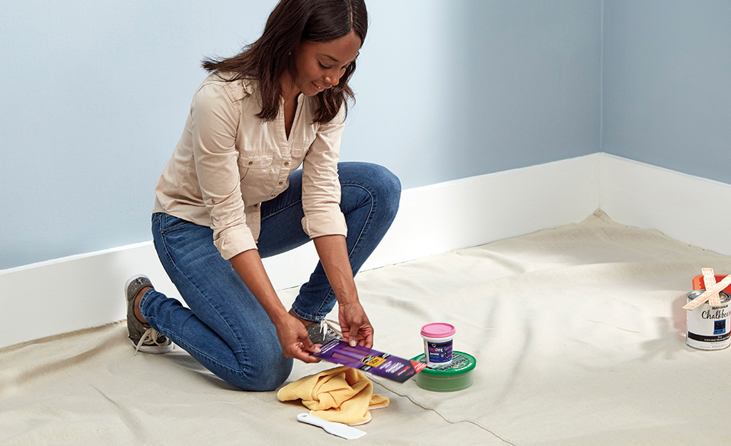 A woman gathers materials for painting a wall.