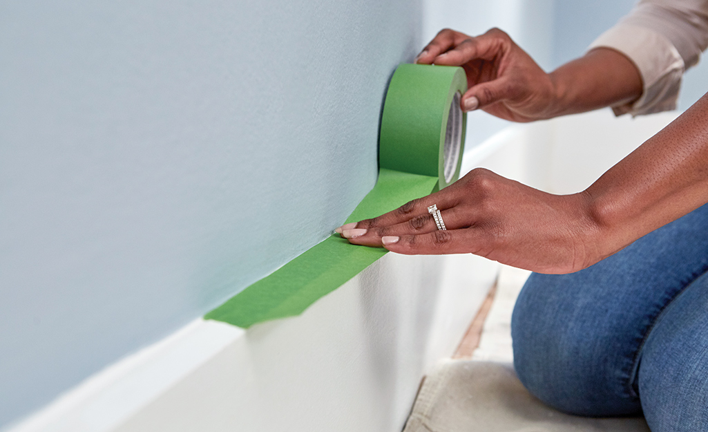 Painter's tape is used to protect baseboards.