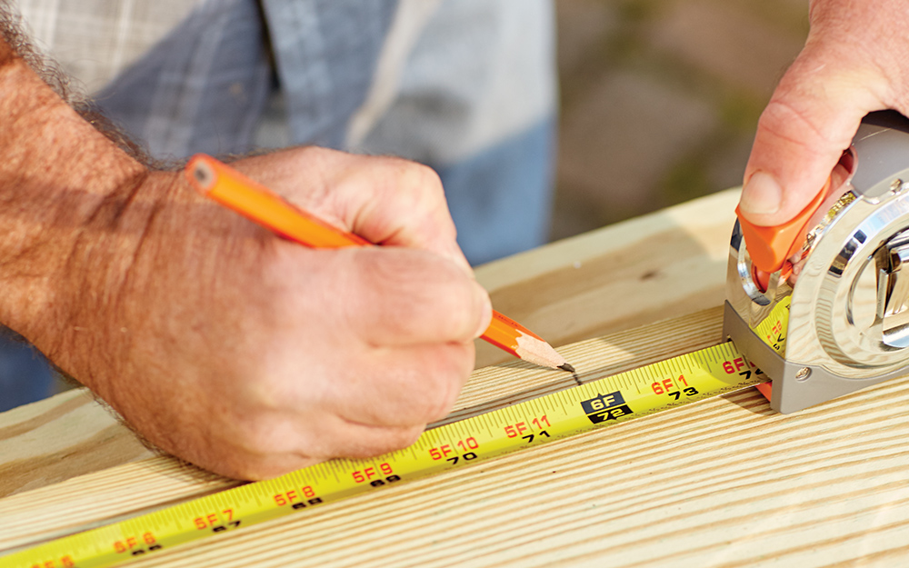 A person marking off measurements on a piece of wood