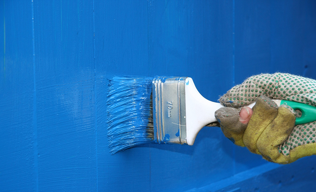 Someone painting a chicken coop blue.