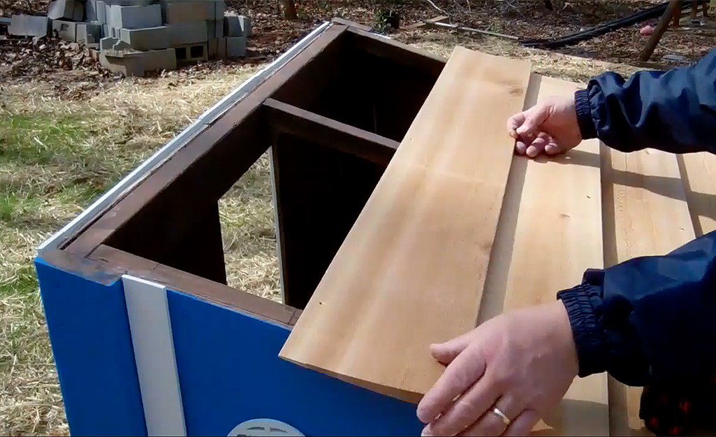 Someone adding a roof to a blue chicken coop.