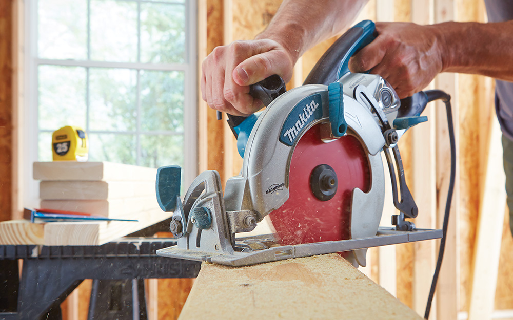 A person cutting a piece of wood with a red-blade circular saw.