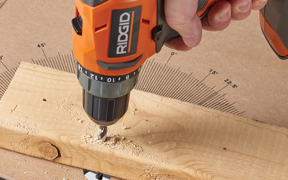A person drilling holes in wood.