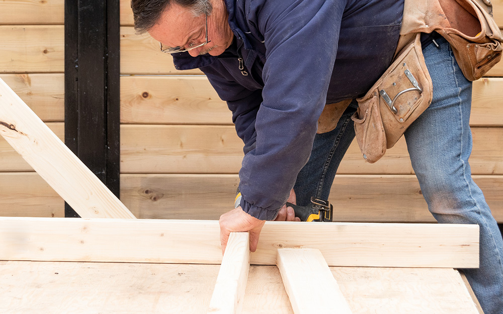 A person lining up pieces of a wooden frame.