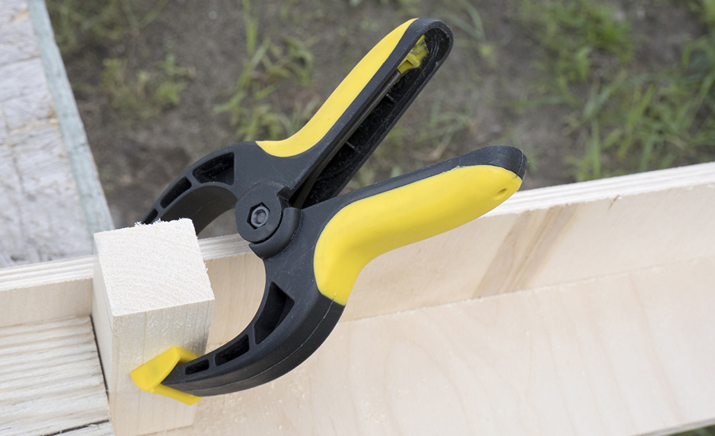 A clamp holding two pieces of wood together.