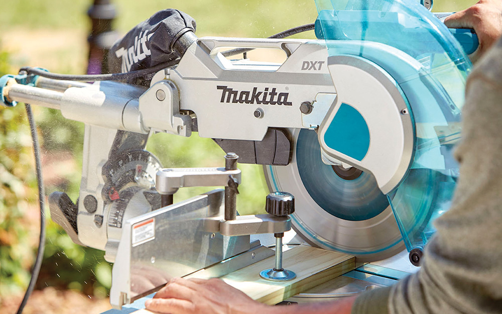 A person using a miter saw to cut wood