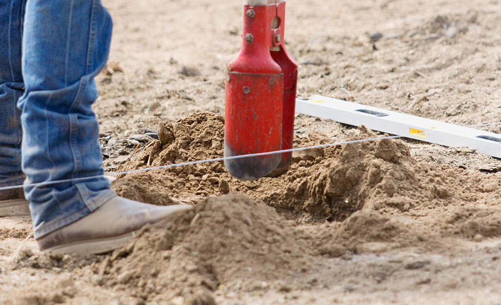A hole being dug in the ground using a post hole digger.