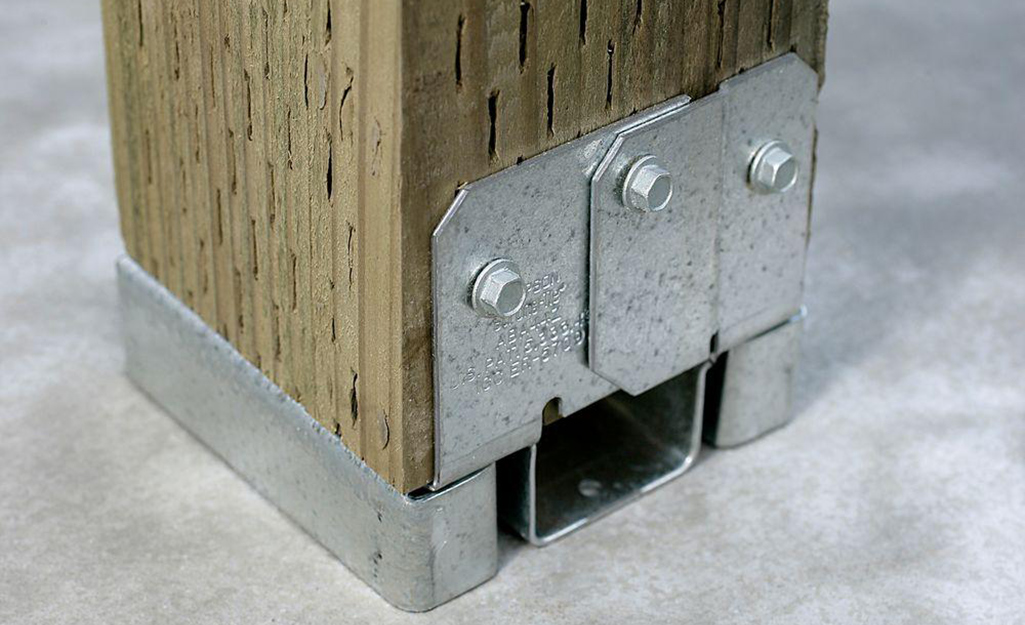 Two people align anchors for deck posts.