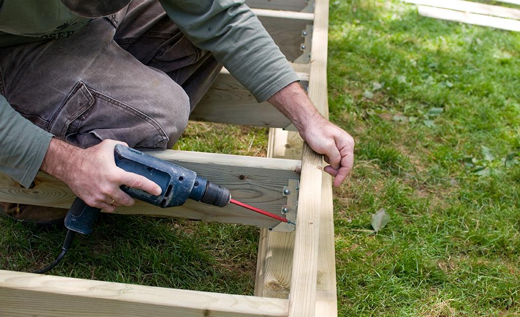 Người đàn ông sử dụng một máy khoan điện để gắn một thanh giằng bên trong của khung boong.