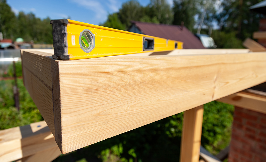 A level being used on a piece of lumber.
