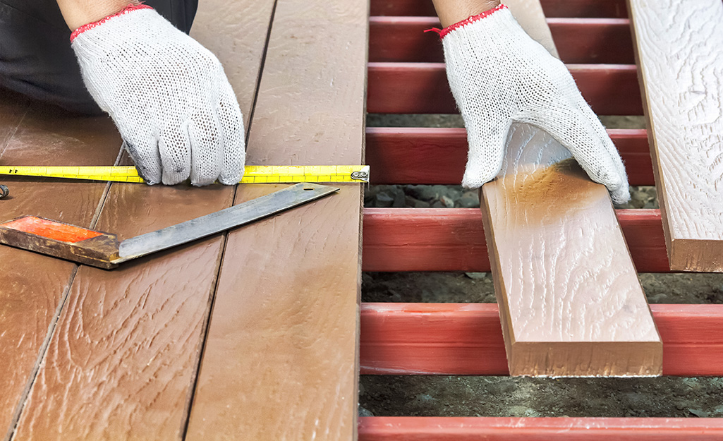 Boards are measured and installed to form a deck.