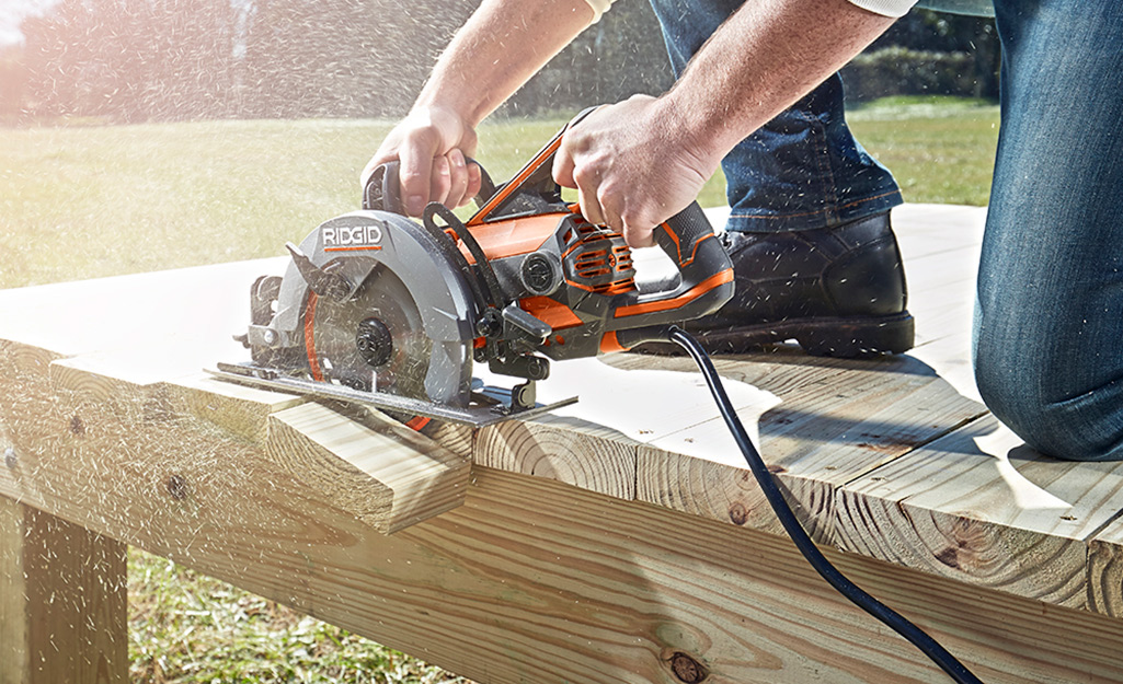 Decking boards are trimmed using a saw.