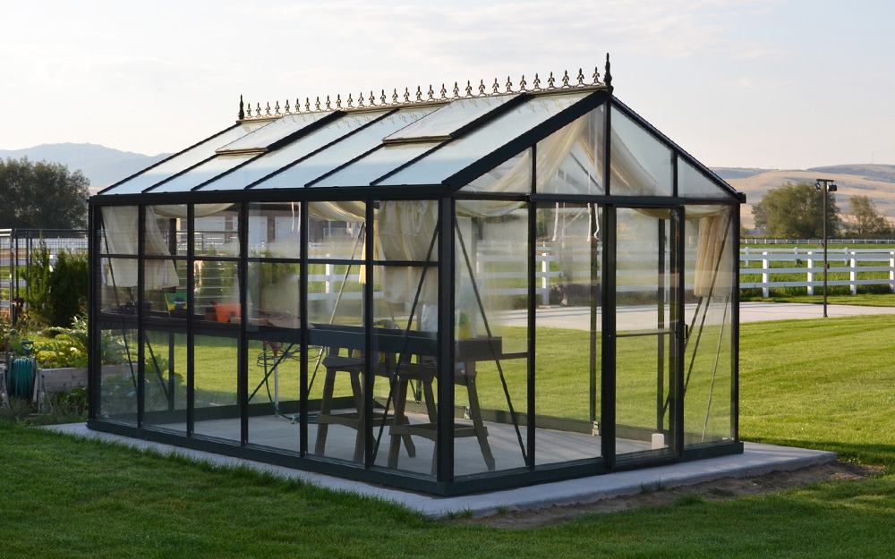 Greenhouse with a black frame and cement foundation.