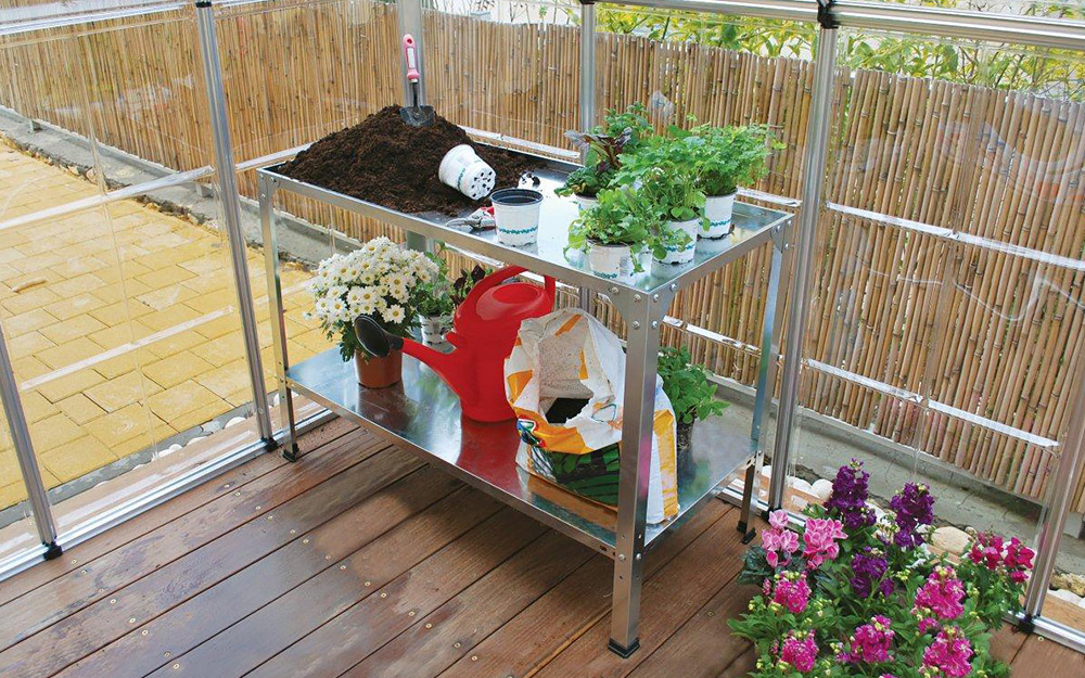 Potting soil, plants and a watering on a greenhouse table with a shelf.