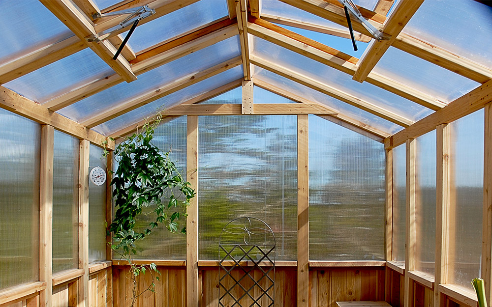 Greenhouse with knee walls built from wood.